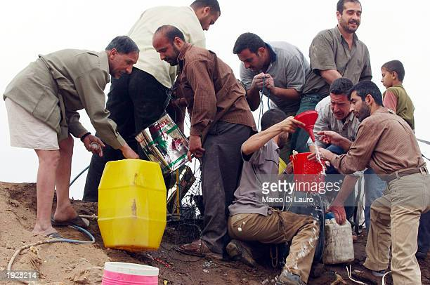 Iraqis loot gasoline from tanks which have been buried underground by the Iraqi regime April 13 2003 in Baghdad Iraq Widespread looting continues all...