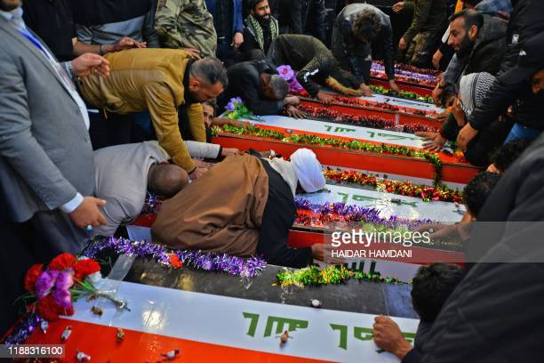 Iraqis mourn by coffins draped in the national flag during a funeral in the central holy shrine city of Najaf on December 13 for fighters of the...