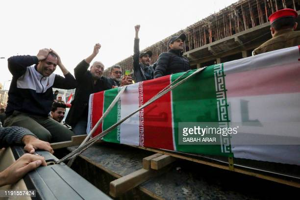 TOPSHOT Iraqis mourn over a coffin during the funeral procession of Iraqi paramilitary chief Abu Mahdi alMuhandis and Iranian military commander...