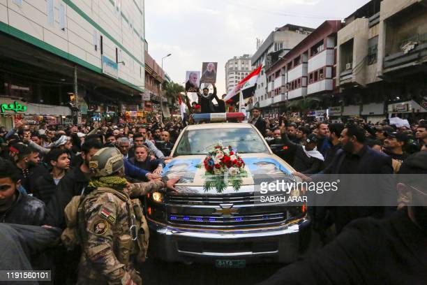 Iraqis mourn over a coffin during the funeral procession of Iraqi paramilitary chief Abu Mahdi alMuhandis and Iranian military commander Qasem...