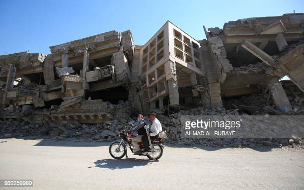 TOPSHOT Iraqis pass destroyed buildings in the old city of Mosul on March 14 eight months after the Iraqi government forces retook the city from the...