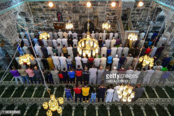 Iraqis perform the Eid AlAdha morning prayer at alBasha mosque in the eastern side of Iraq's northern city of Mosul on August 11 2019 Muslims across...