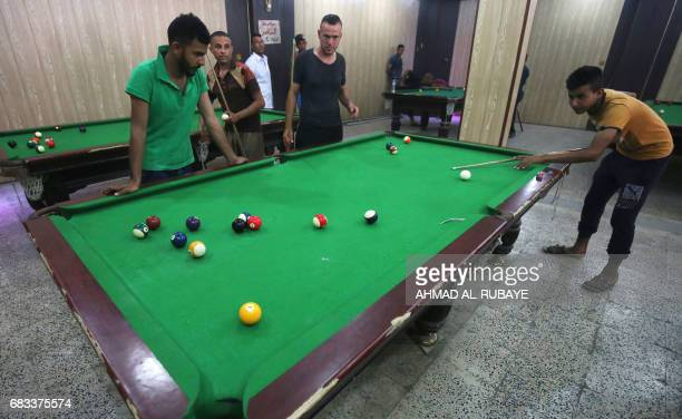 Iraqis play pool on May 15 2017 in Mosul's neighbourhood of alJadida as civilians gradually return to the area after Iraqi forces recapture the...