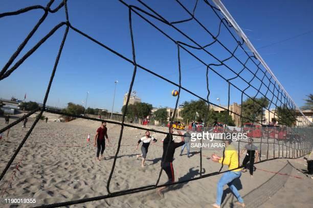 TOPSHOT Iraqis play volleyball as they wind down on the bank of the Tigris river in the capital Baghdad on december 21 2019 In the heart of Baghdad a...