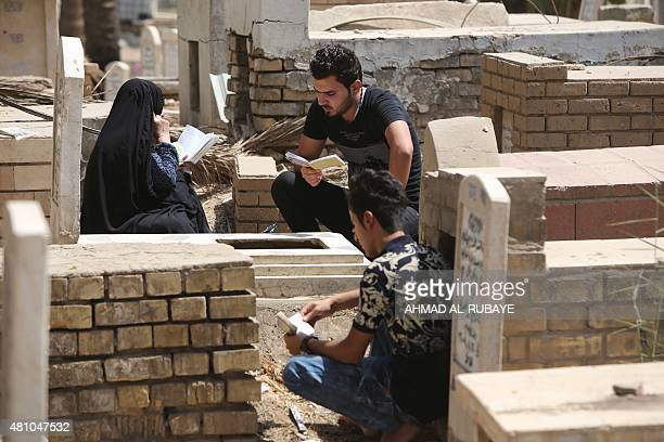 Iraqis pray as they visit the graves of loved ones at a cemetery in the capital Baghdad on July 17 2015 on the first day of Eid alFitr holiday that...