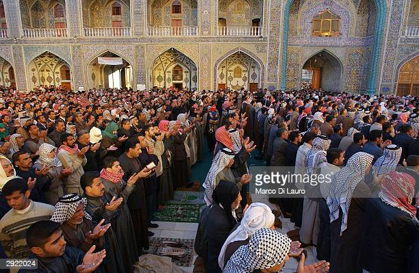 Iraqis pray at the shrine of Imam Ali during a prayers held to celebrate Eid alAdha on February 2 2004 in Najaf 180 km south of Baghdad Iraqis from...