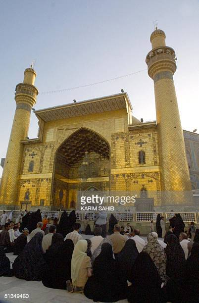 Iraqis pray in front of the shrine of Imam Ali the cousin and soninlaw of Islam's Prophet Mohammad in Iraq's holy Shiite city of Najaf some 180 kms...