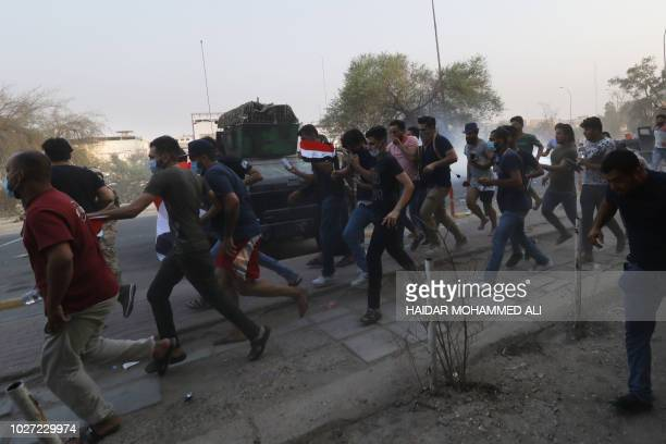 Iraqis protestors run as security forces disperse a demonstration against the government and the lack of basic services in the southern city of Basra...