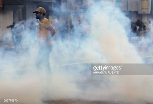 Iraqis react to tear gas fired by Iraqi security forces during a demonstration against unemployment and a lack of basic services in the capital...