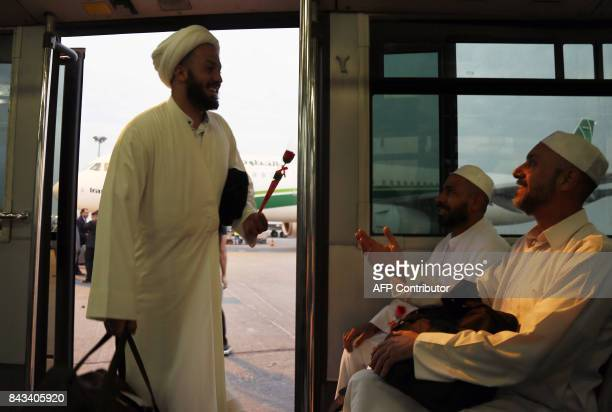 Iraqis returning from the annual Muslim Hajj pilgrimage in Saudi Arabia share a light moment after disembarking from an Iraqi Airlines plane at the...