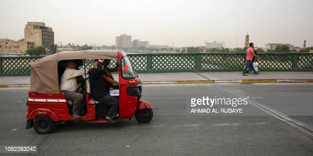 Iraqis ride a motorised rickshaw across a bridge on the Tigris river in the capital Baghdad on October 16 2018