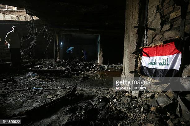 Iraqis search for bodies of victims on July 4 2016 inside a building damaged by a suicidebombing attack which took place a day earlier in Baghdad's...
