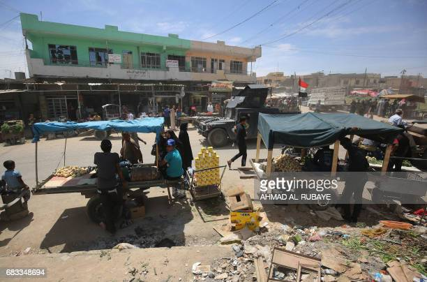 Iraqis sell goods on May 15 2017 in Mosul's neighbourhood of alJadida as civilians gradually return to the area after Iraqi forces recapture the...