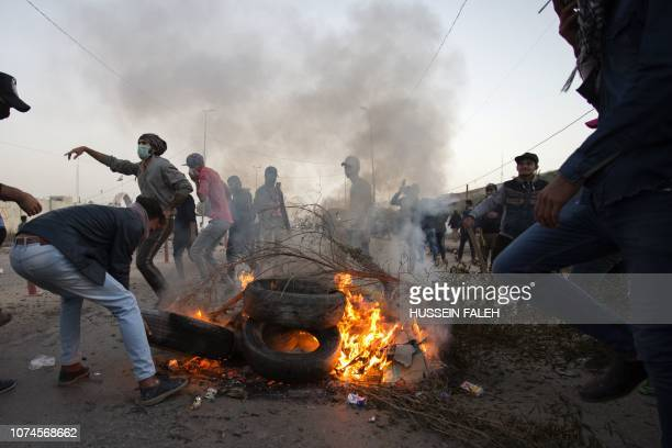Iraqis set tires aflame and block a road as they protest against corruption and unemployment in the southern city of Basra on December 21, 2018.