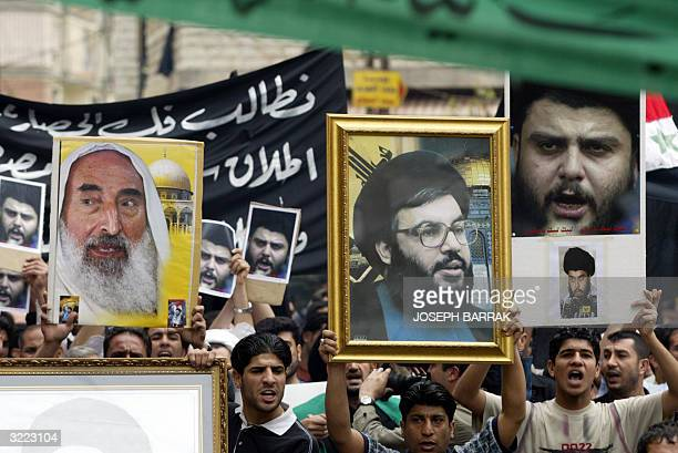 Iraqis Shiite protesters carry up pictures of late Hamas spiritual leader Sheikh Ahmed Yassin Hezbollah secretary general Sheikh Hassan Nasrallah and...