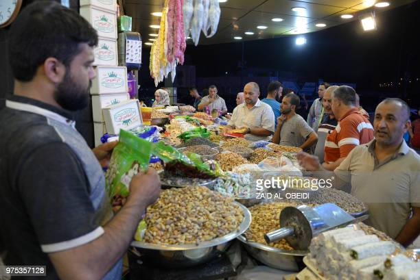 Iraqis shop for nuts sweets and dried fruits at a market on the last day of the Muslim holy month of Ramadan before celebrating the first day of the...