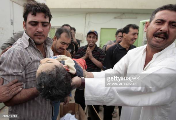 Iraqis show a dead child before they lay his body in a casket next to his father's outside Baghdad's Sadr City hospital on April 30 2008 Both were...