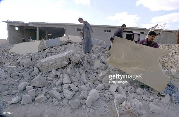 Iraqis sift through the rubble of a destroyed house Janauary 21 2001 in Samawa some 186 miles 300 kms south of Baghdad Iraq Iraqi officials say that...