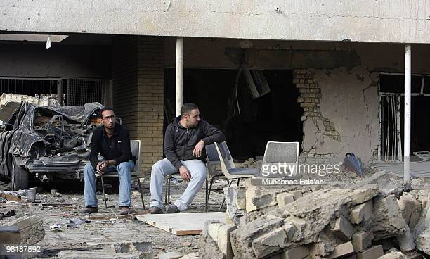 Iraqis sit outside their devastated house after yesterday's car bomb explosion on January 26 2010 near the AlHamra hotel in Baghdad Iraq Three car...