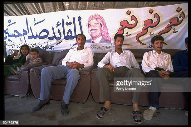 Iraqis sitting in shadow of campaign banner imaging Pres Saddam Hussein on day of yes or no ballot 1cand election
