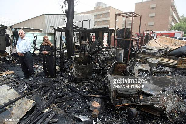 Iraqis stand at the scene of a rocket attack on a residential compound in central Baghdad on July 5 after several Iraqis were killed and wounded...