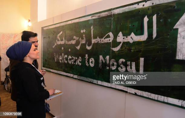 Iraqis stand in front of a 'Welcome to Mosul' road sign displayed on January 29 2019 at an art hall in the museum of the northern Iraqi city of Mosul...
