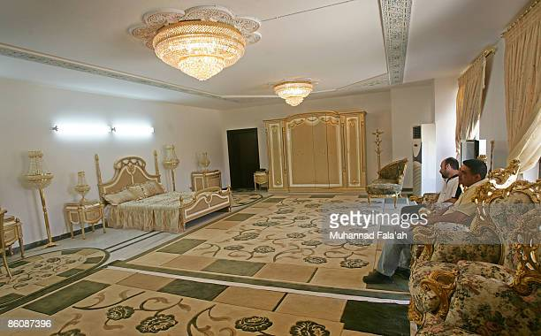 Iraqis stand inside a marbled room where Saddam supposedly once slept at one of the former dictator 's palace villas which can be rented for about...