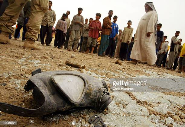 Iraqis stand near a discarded an Iraqi soldier's gas mask April 9 2003 at an Iraqi military post in Amarah Iraq The 24th Marine Expeditionary Unit...
