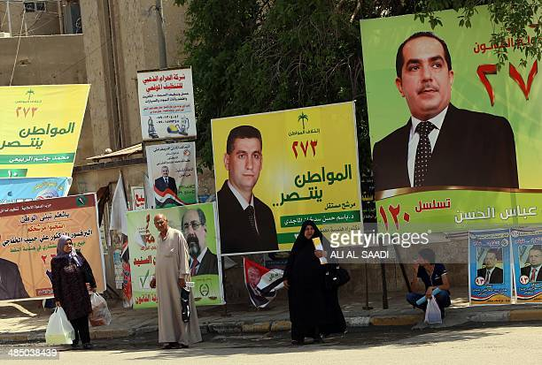 Iraqis stand near campaign posters for Iraq's upcoming general elections in the capital Baghdad on April 16 2014 Campaigning for Iraq's April 30...