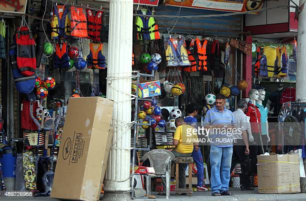 DUNLOP Iraqis stand outside a a shop selling life jackets on Rashid Street where many of the Baghdad's sports shops are located on September 13 as...