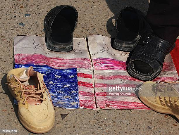 Iraqis step and put shoes on a US flag in protest over the new images of abuse at Abu Ghraib prison on February 17 2006 in the Sadr city neighborhood...
