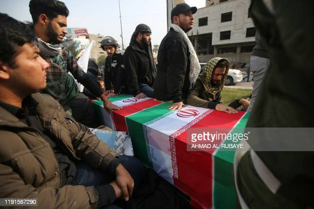 Iraqis surround a coffin draped in an Iranian national flag during the funeral procession of Iraqi paramilitary chief Abu Mahdi alMuhandis Iranian...