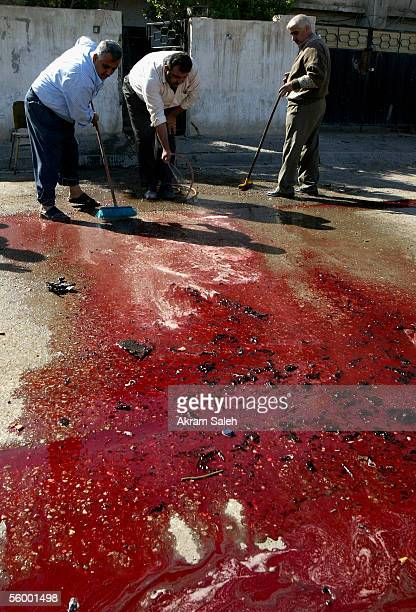 Iraqis sweep a pool of blood away at the scene of a car bomb explosion on October 25 2005 in Baghdad Iraq A car bomb exploded as a US military convoy...
