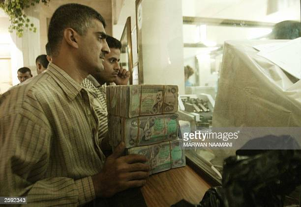 Iraqis wait at a bank counter to chage old dinar bills in Baghdad 15 October 2003 as Iraqi banks began to exchange the country''s old currency...