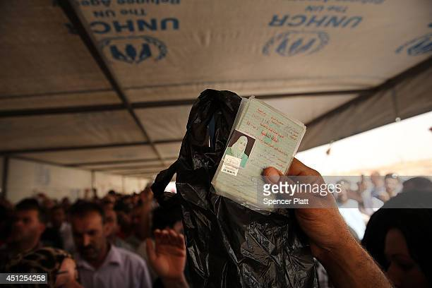 Iraqi's wait in line to register at a temporary displacement camp for Iraqis caughtup in the fighting in and around the city of Mosul on June 26 2014...