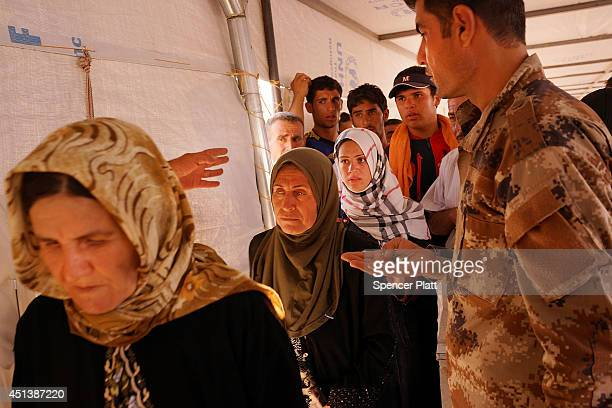 Iraqi's wait to be registered in a displacement camp for those caughtup in the fighting in and around the city of Mosul on June 28 2014 in Khazair...