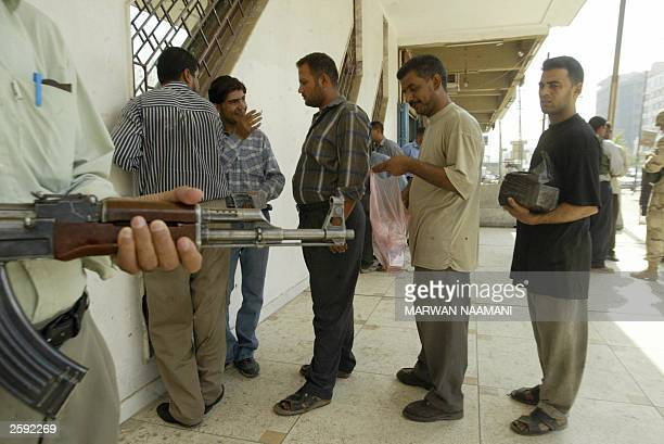 Iraqis wait under heavy security at a bank counter to change old dinar bills in Baghdad 15 October 2003 as Iraqi banks began to exchange the...