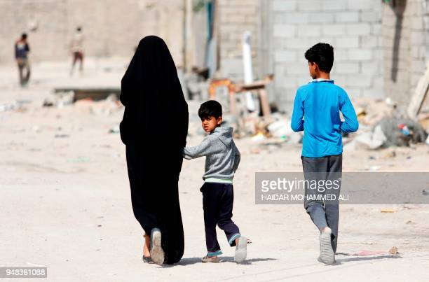 Iraqis walk along the street in alZubair south of Basra on February 11 2018 Informal housing settlements are flourishing in the oilrich province of...