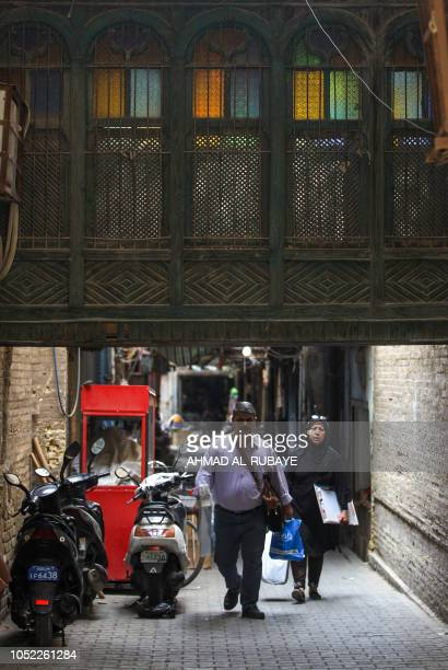 Iraqis walk down an old alley in the capital Baghdad on October 16 2018
