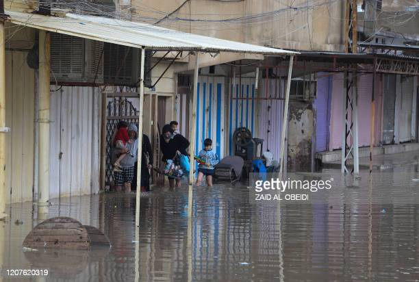 Iraqis walk in a street flooded by heavy rain in the northern city of Mosul on March 18 2020