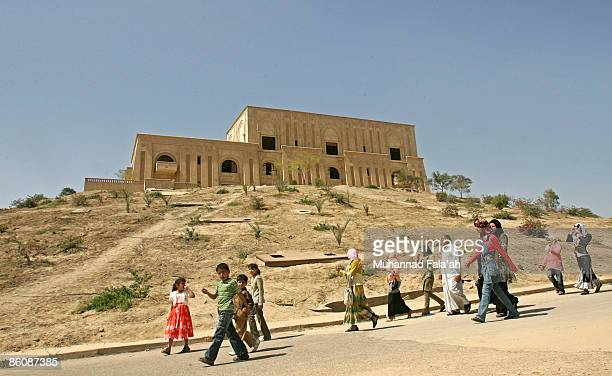 Iraqis walk in front of Saddam Hussein's former palace on April 21 2009 in the city of Hillah in Babil province about 50 miles south of Baghdad Iraq...