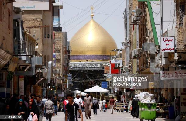 Iraqis walk near the Immam Ali shrine in the holy city of Najaf 150 kilometres south of Baghdad on August 16 2018 In the covered alleyways of old...