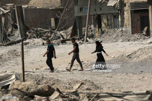 TOPSHOT Iraqis walk on a damaged street in west Mosul on July 13 a few days after the government's announcement of the liberation of the embattled...