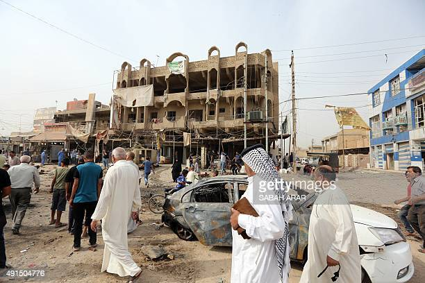 Iraqis walk past a burnt vehicle on October 6 a day after a car bomb explosion in a busy area in Hosseiniyah barely 20 kilometres north of Baghdad...