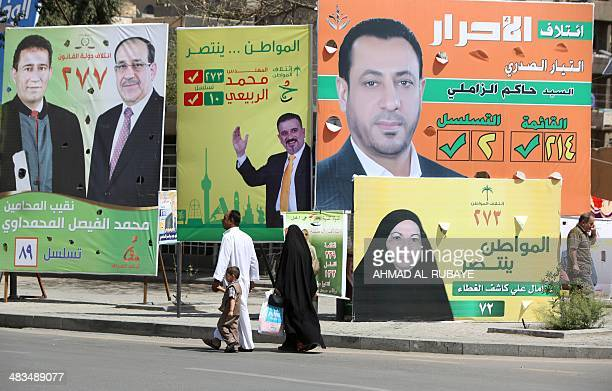 Iraqis walk past election campaign posters at Tahrir Square in Baghdad on April 9 2014 Iraqis go to the polls on April 30 for parliamentary elections...