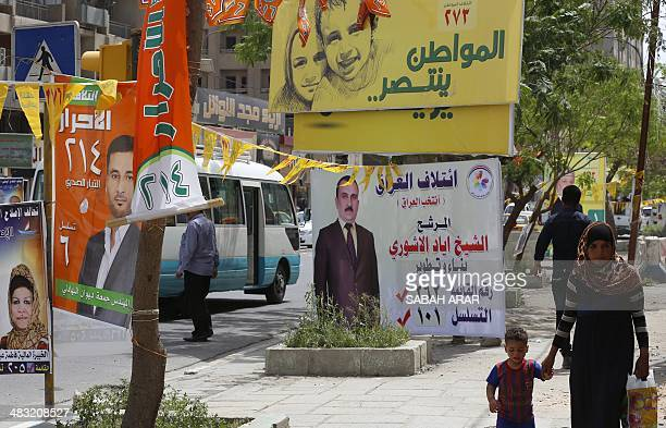Iraqis walk past electoral campaign posters along a street in Baghdad's Karrada central commercial district on April 7 2014 Campaigning for Iraq's...