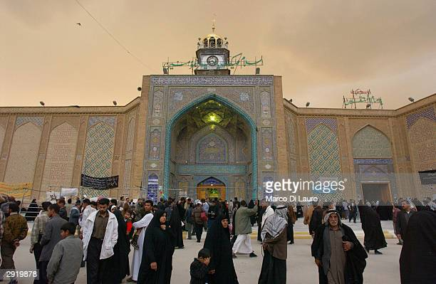 Iraqis walk past the shrine of Imam Ali in Najaf at sunset before a dust storm February 1 2004 in Najaf Iraq Najaf is located approximately 180 km...