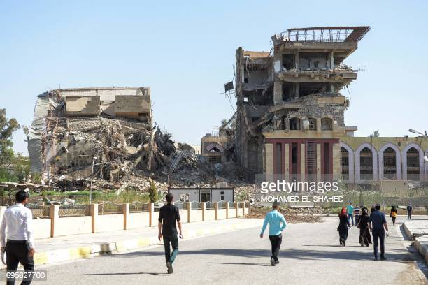 Iraqis walk towards the University of Mosul on June 13 2017 as students arrive to take their exams Amid buildings destroyed by heavy fighting...