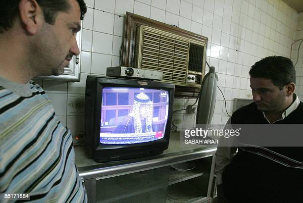 Iraqis watch a television as a sentence is passed on Hassan alMajid known as 'Chemical Ali' and others former leaders in the regime of ousted...