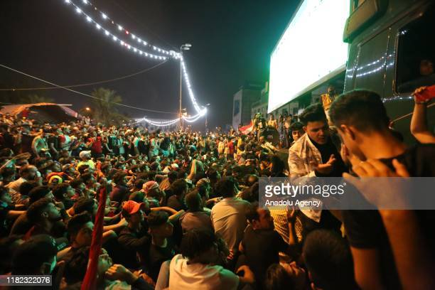 Iraqis watch on a giant screen the Asian Qualifiers for the FIFA World Cup 2022 match between Iraq and Iran, at Tahrir Square in Baghdad, Iraq on...